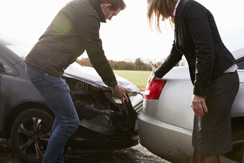两个司机争论关于对汽车的损伤在事故以后 免版税图库摄影