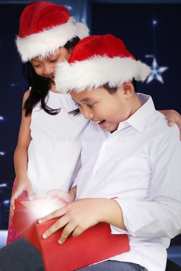 两个吃惊的孩子打开圣诞节礼物 免版税库存照片