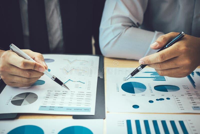 两个商人一起指向公司费用图表和分析的候宰栏财政 库存照片