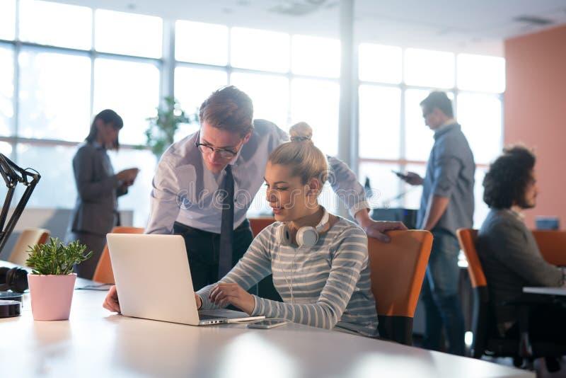 两个商人与膝上型计算机一起使用在办公室 免版税图库摄影