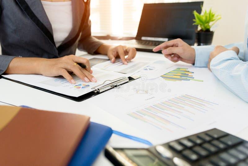 两个商人同事谈论在办公室桌上的计划财政图表数据与膝上型计算机 图库摄影