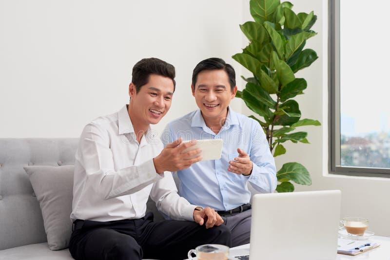 两个商人在办公室工作 到达天空的企业概念金黄回归键所有权 免版税库存照片