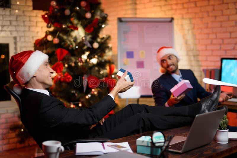 两个商人在新年` s伊芙工作 他们互相吹嘘礼物 图库摄影