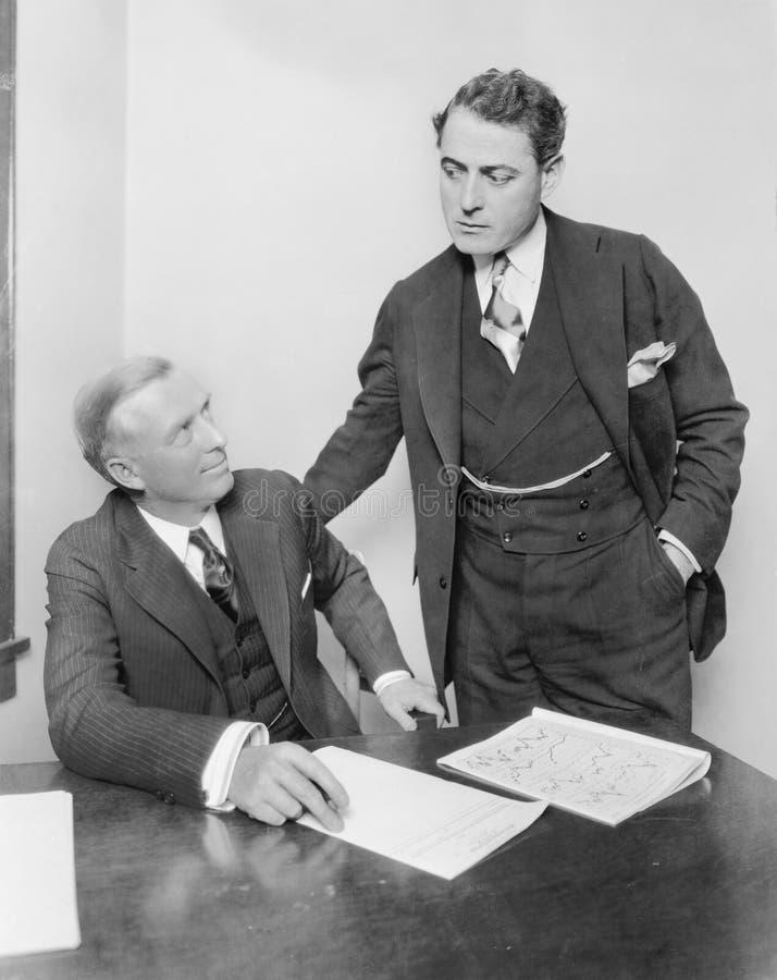 两个商人在有的办公室讨论(所有人被描述不更长生存,并且庄园不存在 供应商warra 免版税库存图片