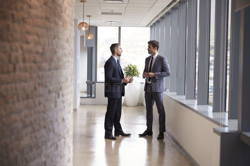两个商人开非正式会议在办公室走廊 库存图片