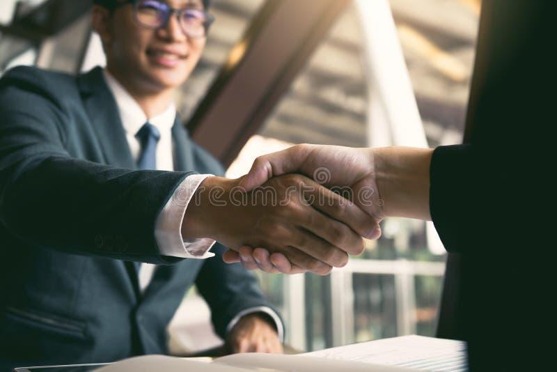 两个商人是谈和做成交在经营活动和同意通过握手在办公室 库存图片