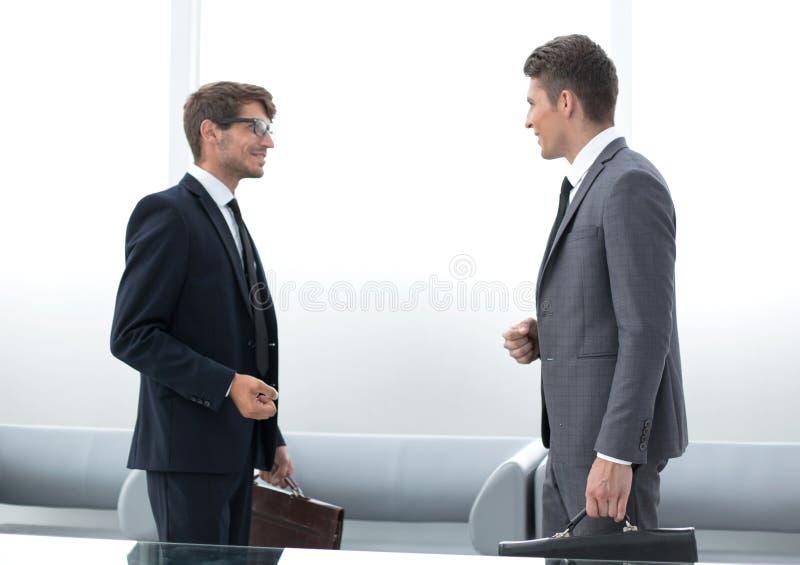 两个商人谈的站立在办公室 免版税库存照片
