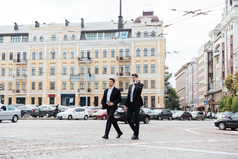 两个商人走和谈话在手机在城市 库存照片