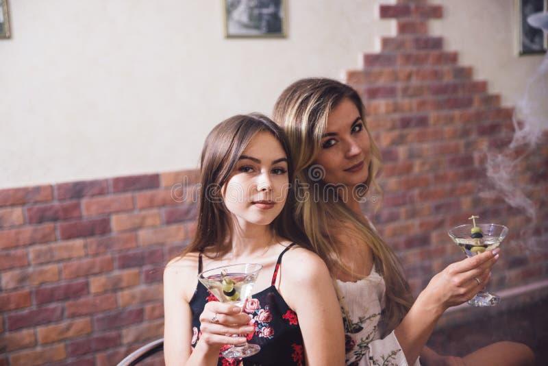 两个在夜总会的女孩在与快餐的一张桌上和水烟筒 库存照片