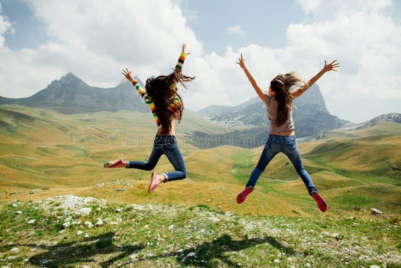 两个在山的女孩愉快的跃迁有扣人心弦的看法 免版税库存照片