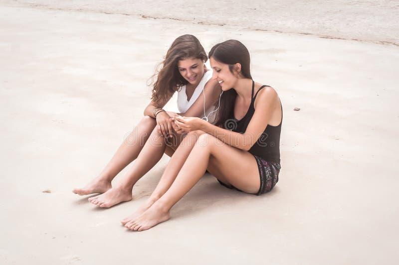 两个在智能手机的最好的朋友听的音乐,享用在海滩 免版税库存图片