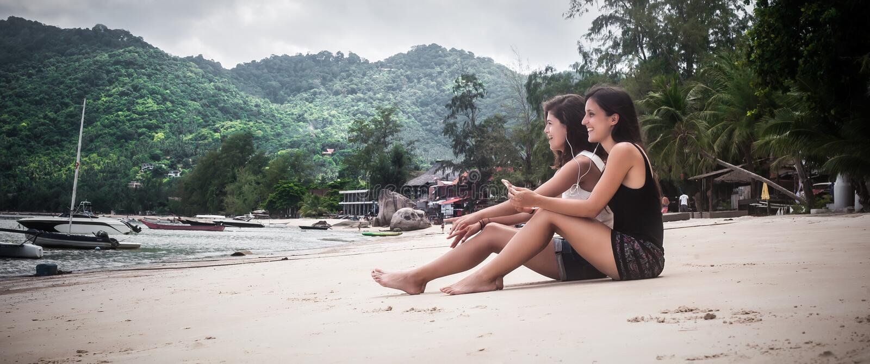 两个在智能手机的最好的朋友听的音乐,享用在海滩 库存图片