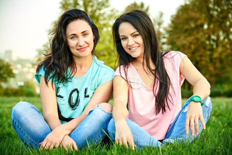两个在草的年轻愉快的女孩谎言 免版税库存图片
