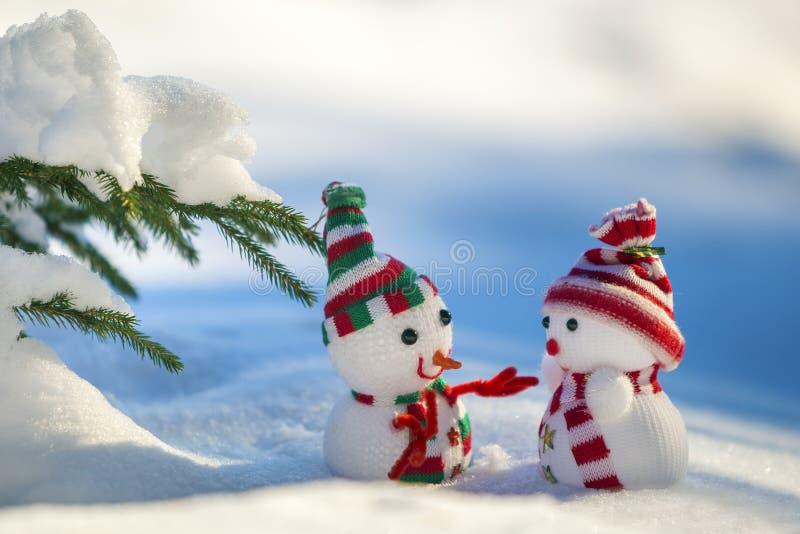 两个在被编织的帽子和围巾的小滑稽的玩具小雪人在深雪户外在明亮的蓝色和白色拷贝空间背景 图库摄影