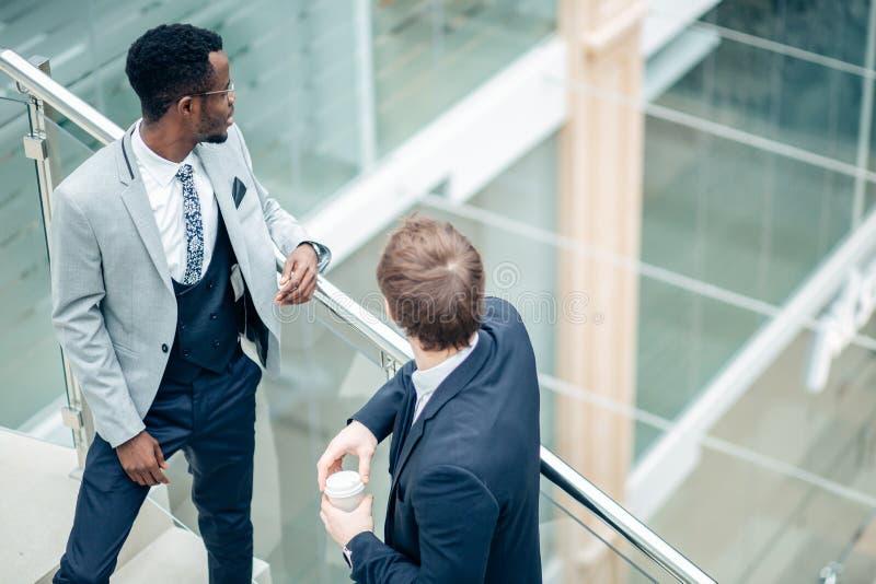 两个多种族商人讨论在现代大厅里 免版税库存照片