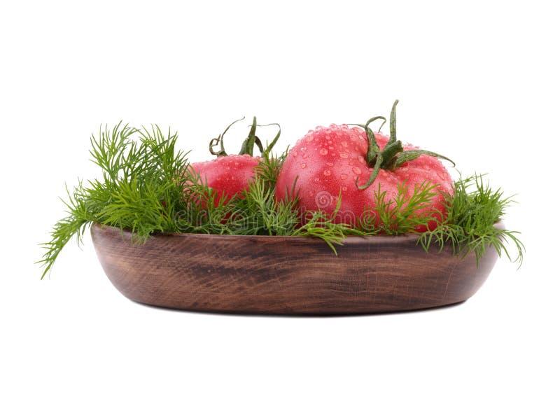 两个大蕃茄用在一个木篮子的新鲜的莳萝,隔绝在白色背景 素食食物概念 免版税库存照片
