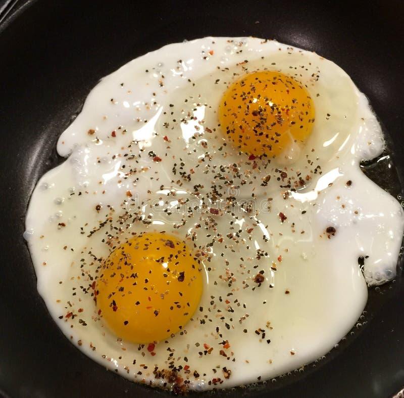 两个大鸡蛋洒与黑胡椒 免版税库存照片