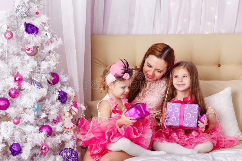 两个女儿的母亲给了圣诞节礼物 免版税库存图片