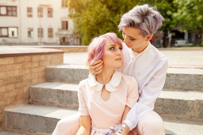 两个女同性恋的女孩坐台阶在城市 库存图片