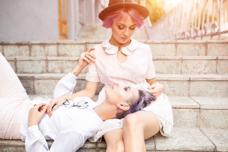 两个女同性恋的女孩坐台阶在城市 免版税库存照片