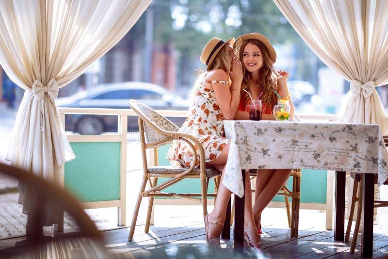 两个女孩分享在坐在咖啡馆的耳朵的一个秘密 免版税图库摄影