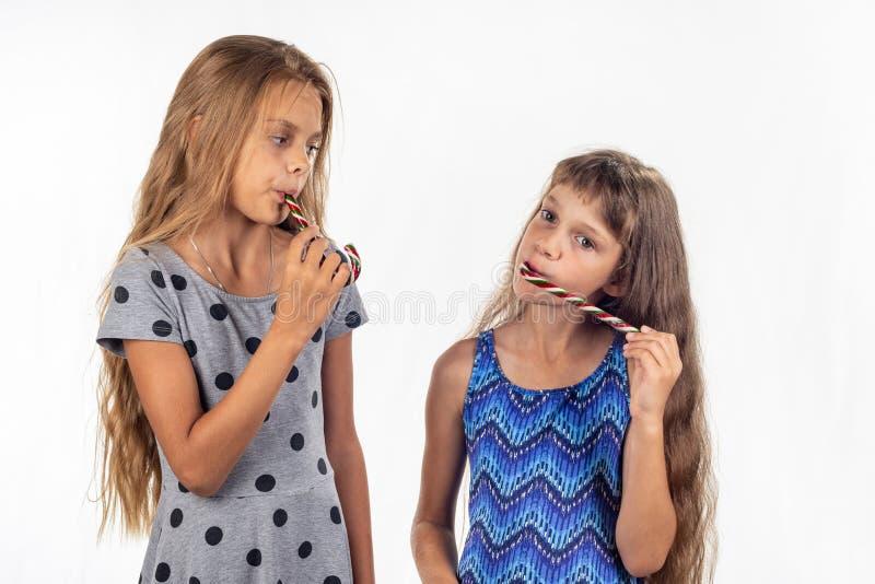两个女孩吮焦糖糖果 图库摄影