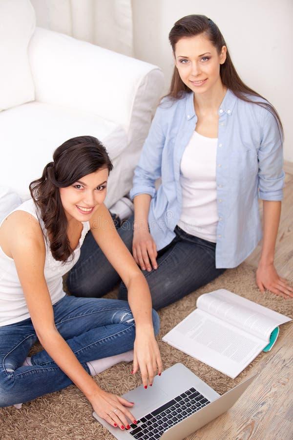两个女孩和膝上型计算机 库存照片