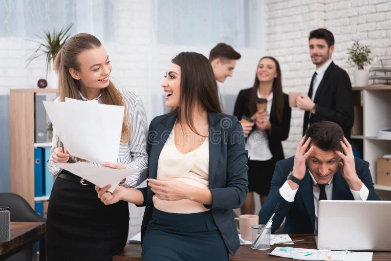 两个女孩嘲笑工作讨厌的上司 年轻人孕妇在有同事的办公室 免版税库存照片