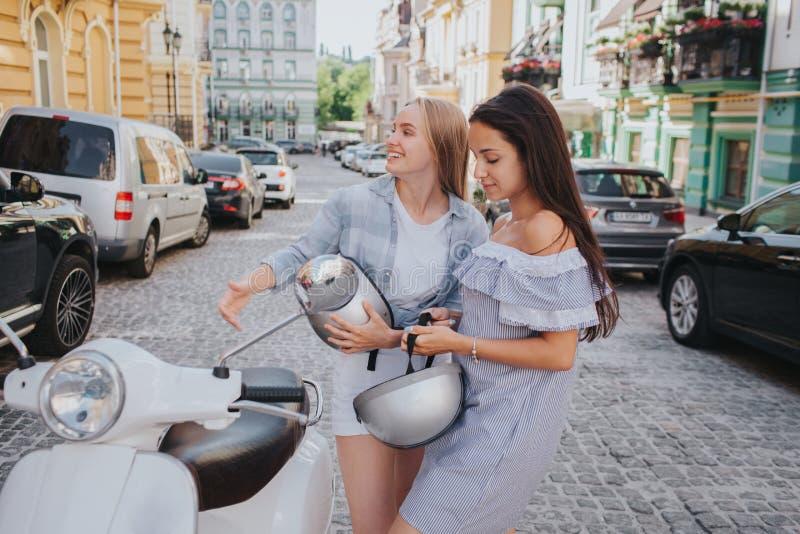 两个女孩在一辆摩托车乘坐 中国女孩是在前面 深色的女孩在中部坐 最后一个 免版税库存照片