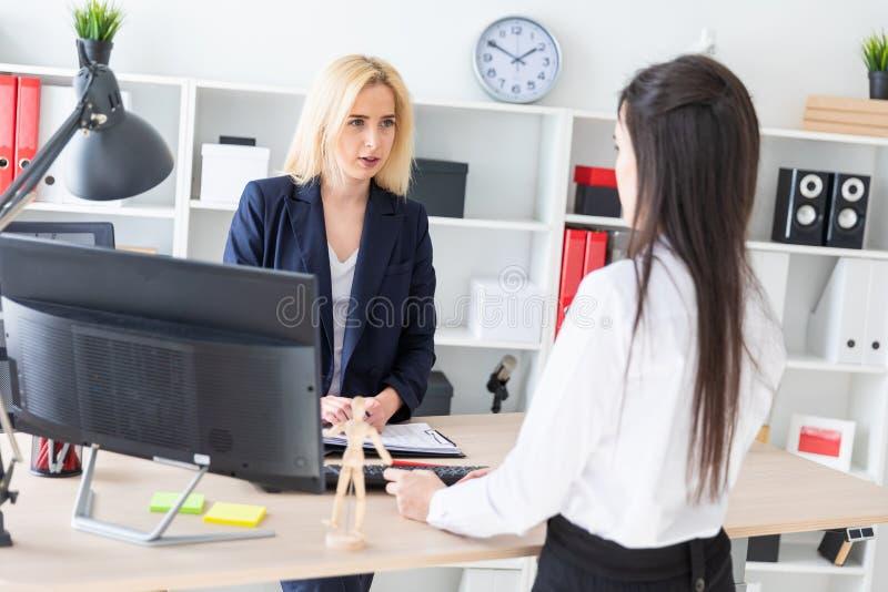 两个女孩在办公室站立在桌附近并且看彼此 库存照片