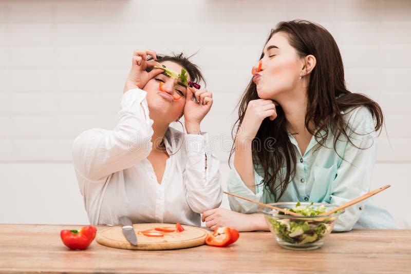 两个女孩在厨房里做与菜的滑稽的面孔 免版税库存图片