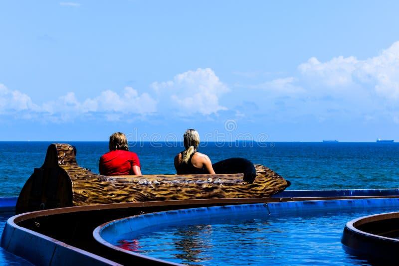 两个女孩在墨西哥湾的乐趣码头敢乘坐海盗` s倾没 免版税库存图片