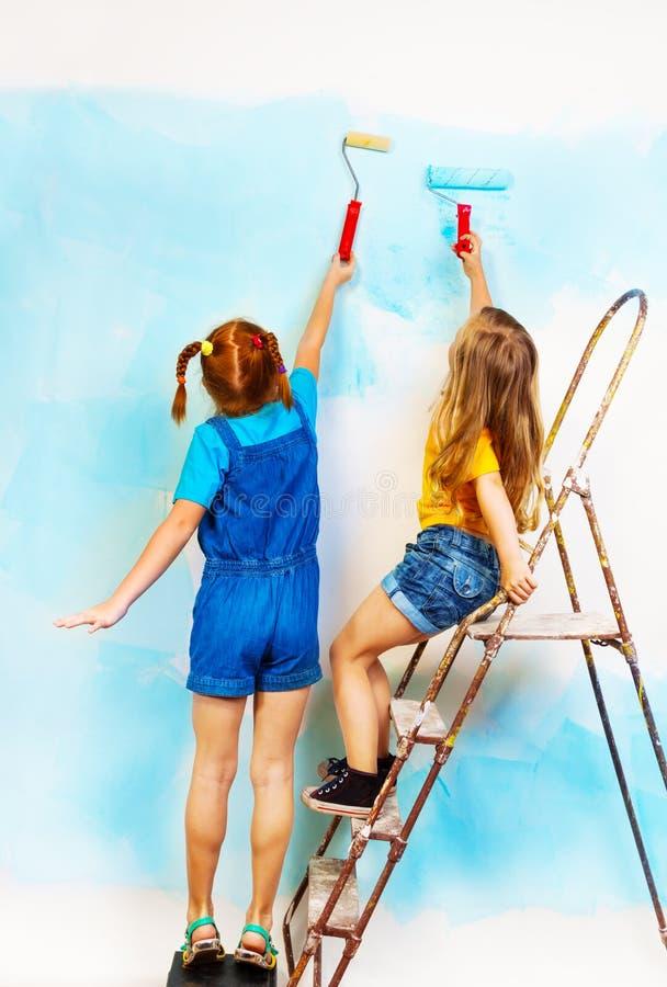 两个女孩在壁架和油漆墙壁上站立 免版税库存图片