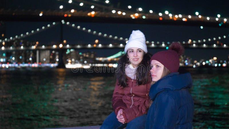 两个女孩在夜之前探索纽约这里在布鲁克林大桥 免版税库存图片