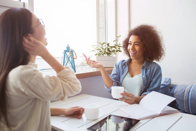 两个女孩在彼此和学习前面坐 并且他们是谈话和laughting 年轻学生神色 免版税库存照片