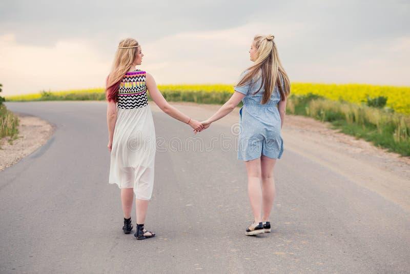 两个女孩在握手的路去 库存照片