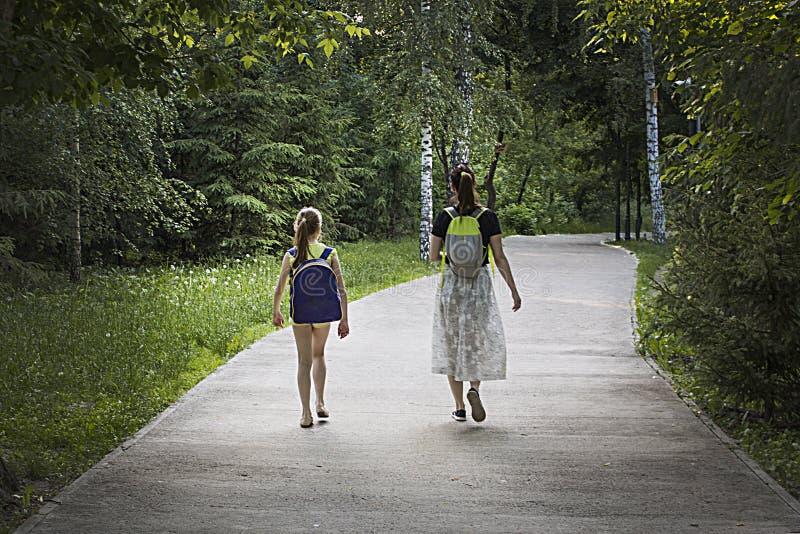 两个女孩在有背包的公园走 免版税库存照片