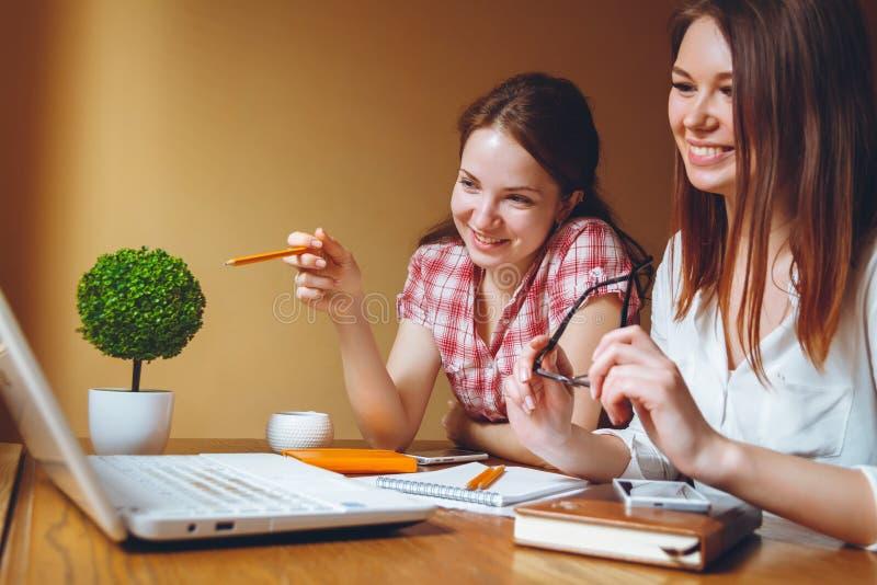 两个女孩在计算机和片剂上的办公室工作 免版税库存照片