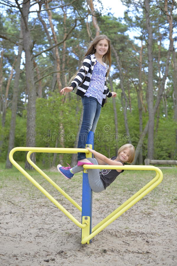 两个女孩在金吸引力的操场使用 它是有风的 免版税库存图片