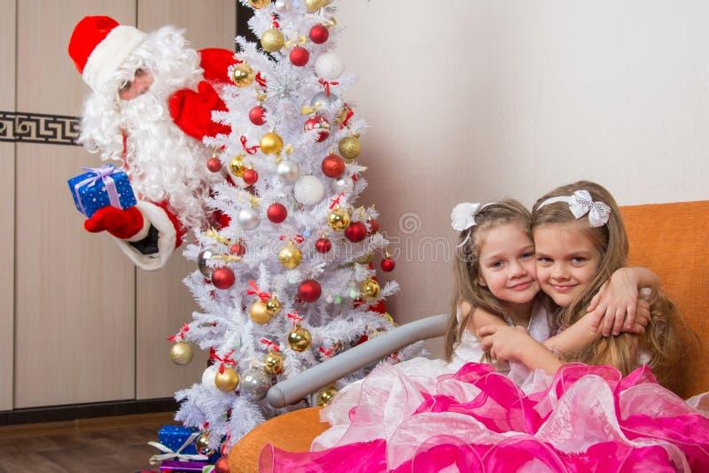 两个女孩在长沙发,偷看从后面树的圣诞老人拥抱 图库摄影