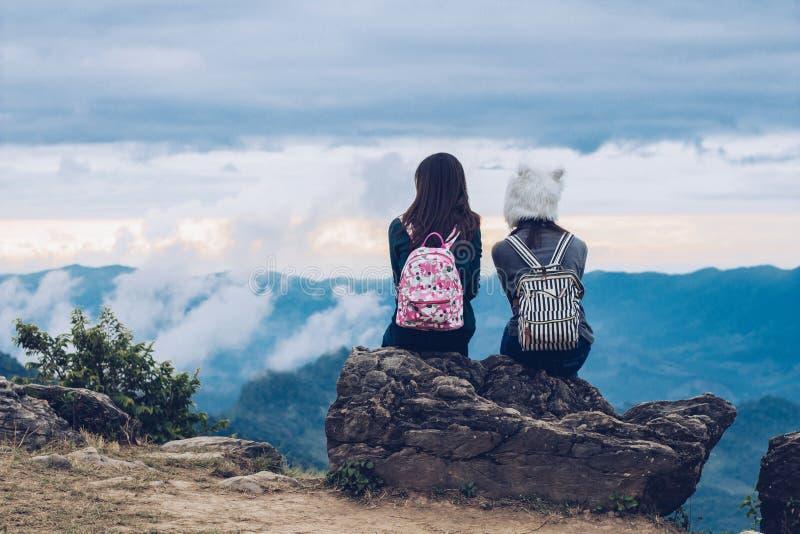 两个女孩坐从上面看与云彩的,天空蔚蓝和绿色树美丽的景色的岩石 免版税库存照片