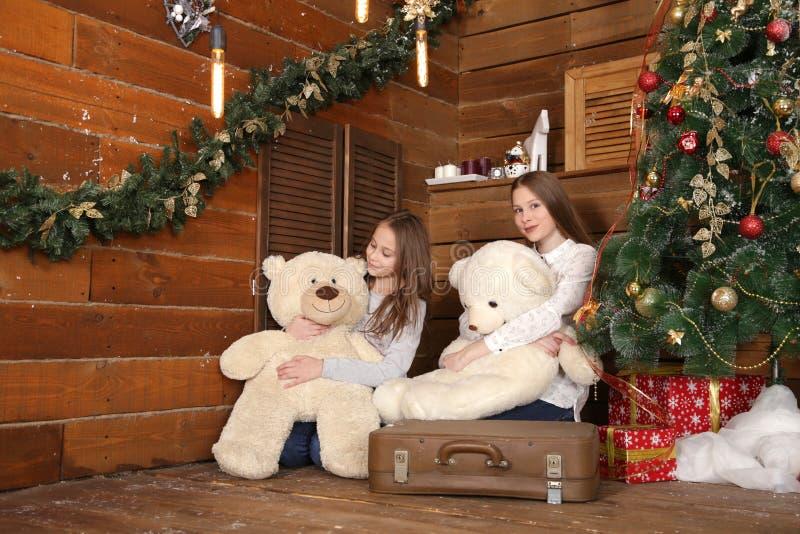 两个女孩坐在木墙壁的背景的地板在圣诞树附近 免版税库存图片