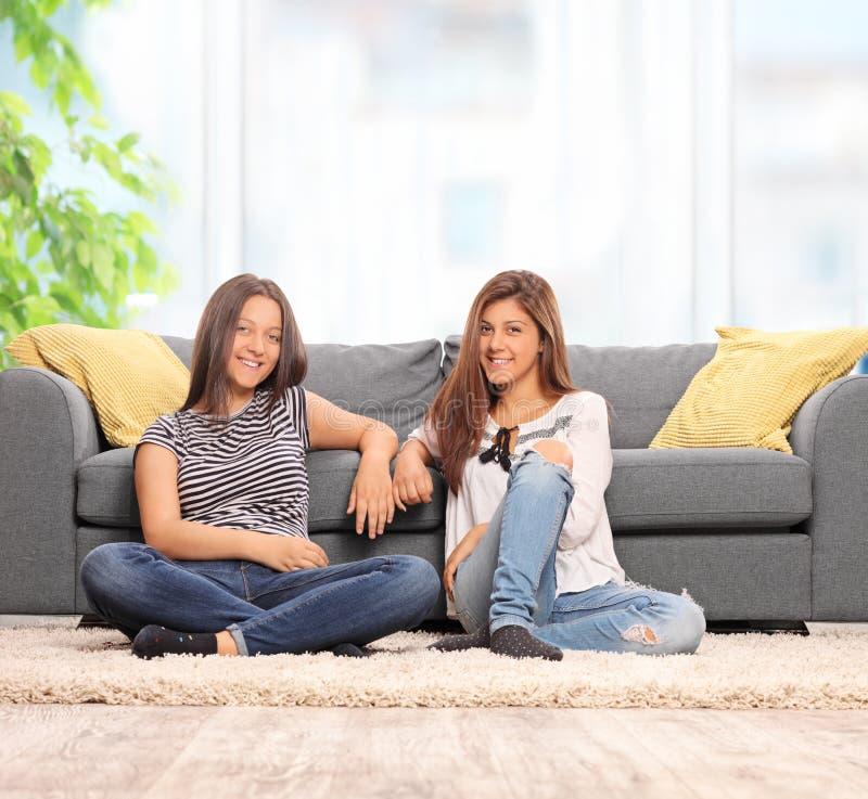 两个女孩坐在长沙发前面的地板 免版税库存图片