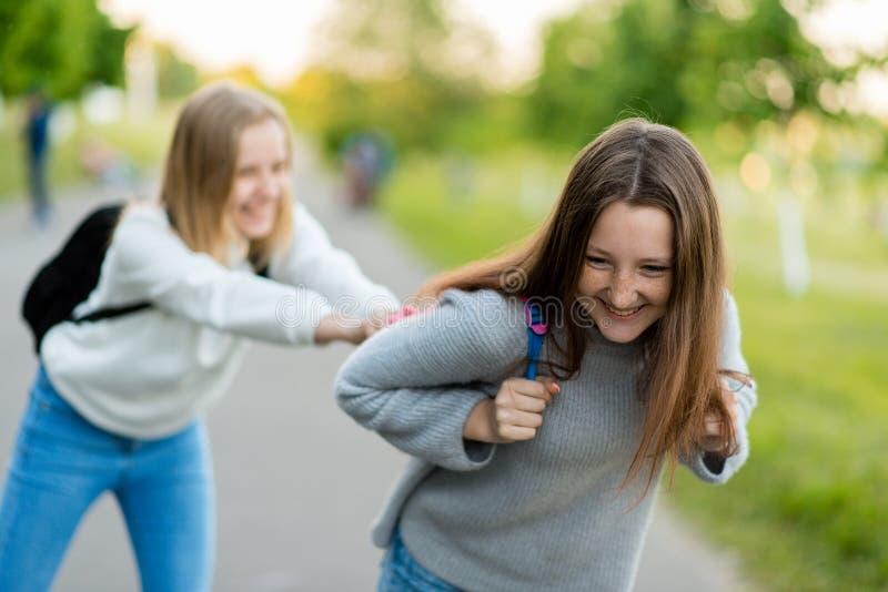 两个女孩女小学生 最佳的女朋友 在夏天,公园本质上 获得在街道上的乐趣 概念是最佳 免版税库存图片