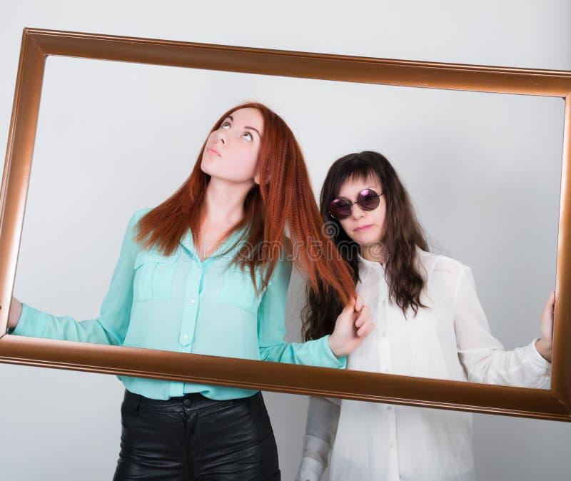 两个女孩女朋友进入图片,有乐观的夫人的框架解答和乏味,懊恼无知哀伤 库存照片