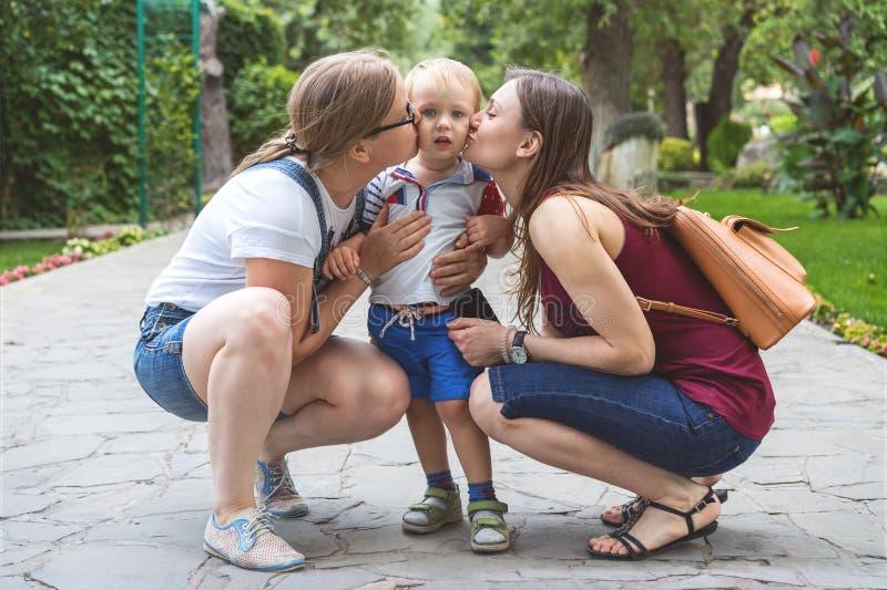 两个女孩妈妈亲吻他们反复无常的小男孩孩子在公园 不是一个传统家庭 免版税库存照片