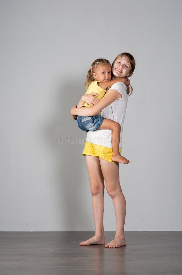 两个女孩姐妹少年和孩子 免版税库存图片