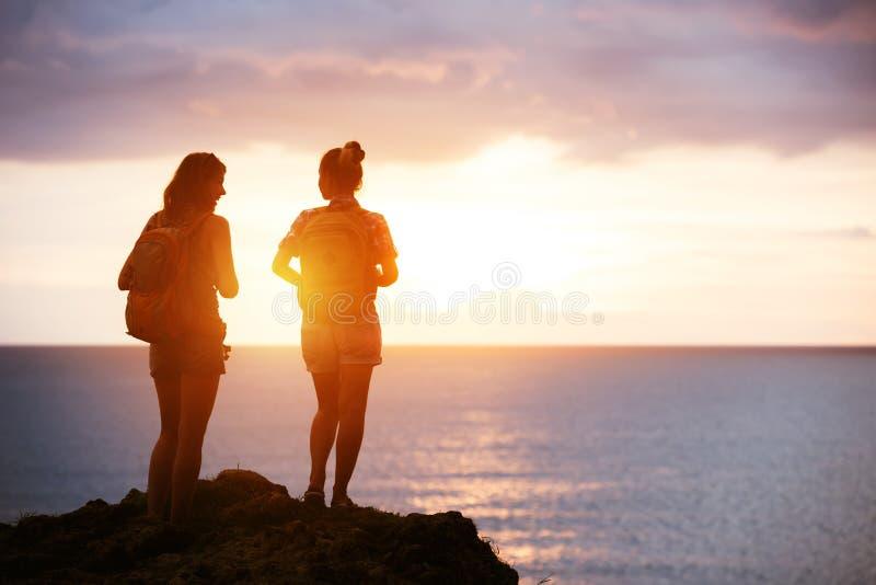 两个女孩旅行海日落概念 免版税库存图片
