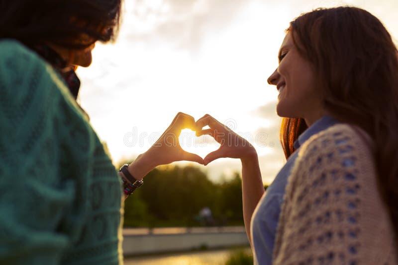 两个女孩显示从手的心脏在日落 免版税库存照片