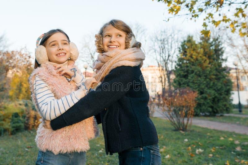 两个女孩最好的朋友,拥抱的微笑的女孩室外画象观看日落,晴朗的秋天冬天公园 免版税图库摄影